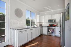 Contemporary Kitchen with Hardwood floors, flush light, Dupont Dove Corian, Flush, European Cabinets, Subway Tile, U-shaped