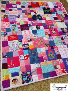 Baby clothes quilt by Lux Keepsake Quilts -- I like how the simple 4-patches are mingled in with the bigger squares/blocks with large motifs on them.