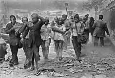People covered in dust walk over debris near the World Trade Center in New York City, on September 11, 2001. (AP Photo/Gulnara Samoilova)