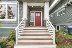 Wide stairs and a red door make for a welcoming entrance.