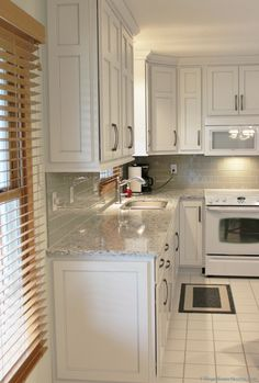 """White kitchen cabinets with gray """"Smoke"""" highlights. 