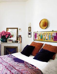 En el rincón del dormitorio se respetó la chimenea original de la casa. Sobre la cama, cuadro oriental recuperado. La colcha estampada es de Antennae y las flores fucsias de Bourguignon