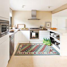 Cocina blanca con suelo de mármol y alfombra de Ikea