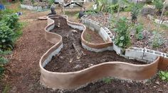 Plastering expanded metal lath with concrete. Paint with lime. Add hugelkultur logs, manure/compost and soil in layers.