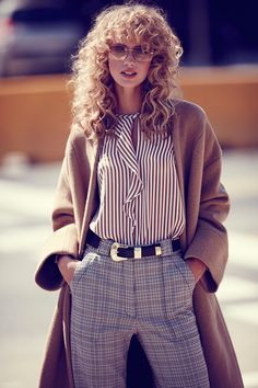 Mixing prints, the model poses in Iro coat, Marella shirt, Sandro pants and Chanel sunglasses