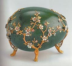 Fabergé Nephrite Easter Egg – Two hollow egg halves in Siberian green jade about 14cm long with four feet in red gold in the shape of apple tree branches. The petals of the white apple flowers are in enamel with their center formed by diamonds on a pink background.