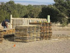 Fence made out of shipping pallets.  I wonder if we could do this in our backyard??