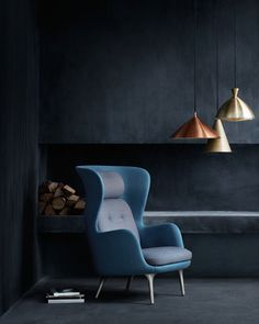 A sombre, dark blue palette for a living space. Copper lamps with a teal arm chair. Fritz Hansen