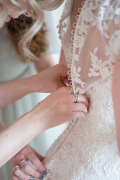 Bridal pre photos of a delicate lace wedding dress being buttoned up by the bridesmaids.