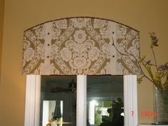 Curtains on arched windows - definitely not this print, but the style could work for making a room dark enough to sleep in.