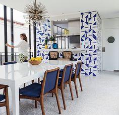 A sala de jantar é iluminada pelo pendente alemão da década de 1960. O painel de azulejos é de Athos Bulcão.