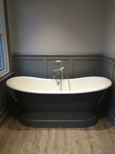 Edwardian bathroom with panelling in Farrow & Ball Manor House Grey, walls in Dimpse. The bath is an Arroll Versailles bath painted in Downpipe. Floor is distressed oak Karndean.