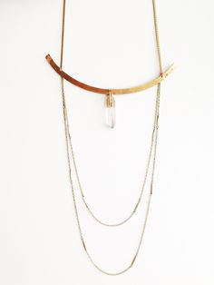 """Clutched quartz crystal suspended from the center of a hand formed and hammered arc.  Opposing hand-stamped arrows mark either end and two tiers of vintage segmented brass chain are suspended underneath. Wear the chains over or under shirt.A small clasp on one side of the arc allows for the necklace to be worn with or without crystal.Necklace chain is adjustable by 1.5"""" Available with either rose or smokey quartz."""