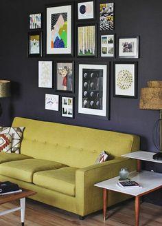 parede pintada de preto, decoração de sala de estar com parede preta, sofá amarelo, mesa lateral com pés de madeira, parede com quadros com molduras pretas