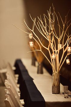 bleached branches with tealight lanterns. don't like it as a centerpiece necessarily but just to sit around the reception area.