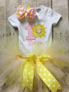 This listing is for a 3 PIECE SET... Includes a Bodysuit/Shirt, Tulle Tutu & Boutique Headband in theme You are my Sunshine. 1st Birthday Bodysuit with number one and sun appliques. Bodysuit is white. The picture shown is an example and the fabrics may no longer be available. The colors of the fabrics and thread may be customized to your color choice. Please message me with your special request. No additional charge for change. If you do not specify, you will receive in colors shown...