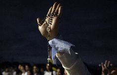 A woman rises a rosary while praying at dawn at Nu Guazu field in the outskirts of Asuncion, Paraguay