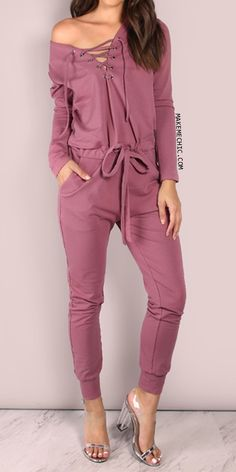 """Cozy on up in this super chic yet effortless ensemble. Featuring a deep v neckline with strappy lace up detailing, long sleeve arms, tieable waist for an extra cinch, two pocket design and a slouchy fit. Jumpsuit measures 57.5"""" in. from top to bottom hem. Keep it casually cool by adorning this garment with gold accents and your freshest pair of kicks."""