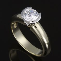 Raised semi bezel set brilliant cut diamond with a tapered band. View your one carat diamond from the side with no prongs to catch.