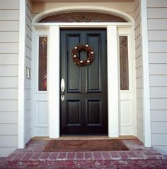 This stylish front door is framed by an arch-shaped transom window and dual sidelights.