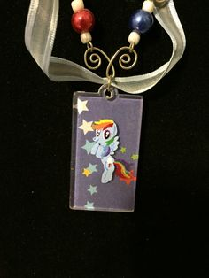 Inspired by My Little Pony!  I am such a huge MLP fan, and I love multi-media projects!  Necklace incorporates wire charms (hand-bent) inspired by Rainbow Dashs Cutie Mark- in this case clouds, and is finished with a ribbon accent.  Beads are on hand-bent wire and are inspired by Dashs coloring.  The charm has a paper background Mod-Podged onto an acrylic charm, filed down at edges to discourage peeling. Each pony is hand-painted by yours truly!  Necklace is approximately 20 inches long…