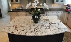 white cabinet with neutral granite, exotic granite with dark island and tile floor