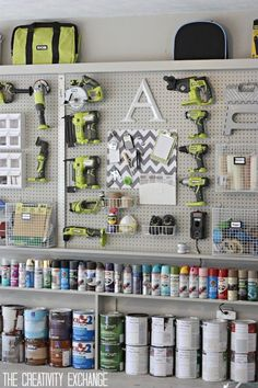 Storage wall in garage with built-in shelving holding paints and spray cans below Home Depot Peg Board which displays tools and wire storage baskets | decorpad.com