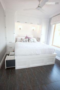 Белая спальня с кроватью с ящиками и шкафами у изголовья. .
