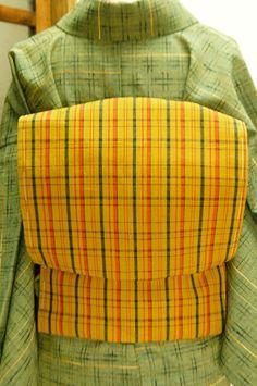 芥子色に近いクロムイエローに黒とバーミリオンレッドのモダンチェックが織り出された綿紬の名古屋帯です。