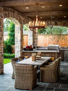 Dining alfresco can be as elegant as indoor dinner parties. Designer Brian Thompson of Thompson Custom Homes creates a rustic outdoor kitchen and dining area complete with chandelier. Blue stone tile grounds the space, while distressed Douglas fir beams on the ceiling and knotty cedar cabinets in the adjacent kitchen give the space a true Old World feel.