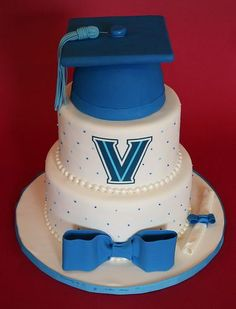 Two tier round white graduation cake with blue cap and bow.JPG