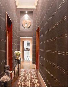 """The entry has been wallpapered in dark brown – with Phillip Jeffries gorgeous – """"Rivets."""" At the end of the hall is the newly renovated kit..."""
