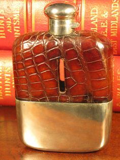 Beautiful Edwardian Period Vintage Glass, Silver Plate & Crocodile Hip Flask England Circa 1910 A beautiful heavy glass antique crocodile hip flask with silver plate bayonet cap and base cup. Removable silver plate base cup that is engraved beautiful decorative floral arrangements. This flask would make a fine gift. The flask is in overall good condition with no chips or cracks, and the cap fits securely and is fluid proof. Dimensions: 5 3/4(14.6cm) high by 4 3/4(12cm) wide and ...