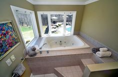 Recessed bathtub with jets and steps with windows that overlook yard