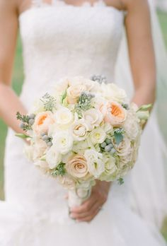 Bouquet of peach and white roses with berry accents from Bella Fioria Floral Design.