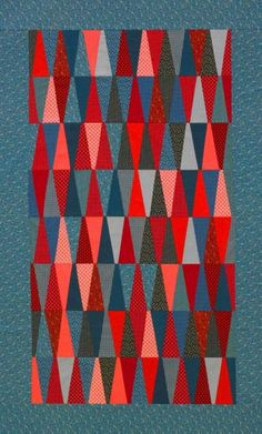 love the colors and the skinny triangles used in this Tumbling Triangles Quilt | AllPeopleQuilt.com