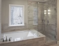 Bathroom remodel by Craftworks Contruction.  Glass enclosed shower, drop in tub surrounded by grey tile, stainless fixtures.