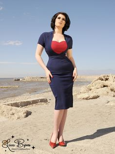 Veronica Dress in Navy with Red Heart  - The Veronica is an hourglass girl's dream in curve-loving bengaline with a nipped-in waistband and an adorable heart-shaped frame at the bust.  Lots of stretch everywhere but the waist, this sexy wiggle will accommodate a range of bust and hip sizes.  Finished off with a charming decorative button detail, front slit, and back zipper.