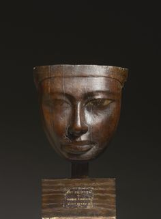 "Exhibitor: Gordian Weber Kunsthandel. Mask of a woman. Wood with dark-brown patina; traces of the original polychromy preserved. 20.3 x 20.5 cm. Old collection label ""ART ÉGYPTIEN / MASQUE FUNERAIRE / XVIII DYNASTI'. Egypt, New Kingdom, Dynasty 18, reign of Amenophis III, 1390-1353 BC."