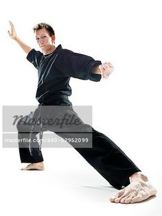 man in a black karate gi practicing martial arts