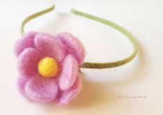 A lovely green tiara with a purple needle felted flower https://www.etsy.com/listing/559835929/purple-flower-tiara-photo-prop-tiara