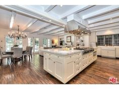 The open-concept kitchen features a gorgeous all-white island with marble countertops.