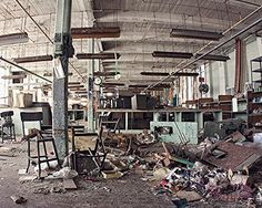 """Abandoned Factory Industrial Urban Decay Urbex Architecture Photography Art Print """"Things Left Behind"""". """"The Things Left Behind"""" is a dark and gritty urban decay photograph of an abandoned garment factory, featuring the things that get left behind... strewn threads, overturned desks and debris littler this once-popular clothing factory. Dark, moody and with a dose of industrial style, this photograph will infuse any living space, office or gallery wall with a bit of historic mystery."""