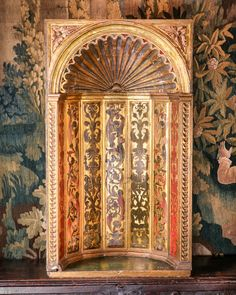 16th century polychrome decorated and parcel gilt pine wall niche. The scalloped dome beneath leaf and berry carved spandrels, above an interior of seven slender planks applied with edge mouldings decorated with renaissance foliate and figural motifs, and botanical imagery. Note: this is a type of niche that would have been in Henry VIII's palaces, …