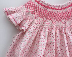 This precious angel wing bishop dress is perfect for spring and can then be worn all summer long! It is smocked by hand in bright pink and finished with French seams and a 3 inch hem. The fabric is white with tiny pink heart shaped flowers on it. The additional detailing on the sleeves and hemline adds that extra touch!  Size 3- Dress measures 23.5 inches from the shoulder to the hemline.  If you are interested in a matching sister dress, please reach out and I will be happy to see if I can…