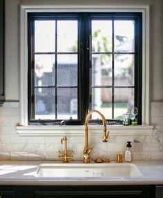 gold faucet.  marble backsplash.  black mullion window. via habitually chic.