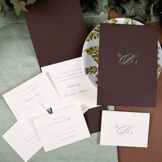 A brown pocket features your monogram on the front printed in foil, tucked inside is an ecru invitation card. Matching enclosures are sold separately.