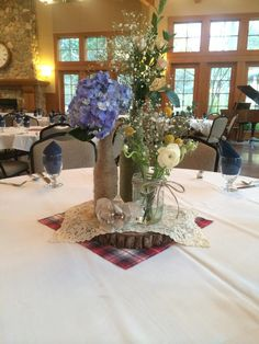 Stef and Jason's Centerpiece - They made the Wood planks and put the twine around the bottles. The tall bottle is chablis spray rose and babies breath. The middle bottle is a shocking blue Hydrangea and the mason jar is dried Billy Balls, babies breath and a white ranunculus.