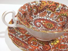 The richness of chintz paisley is dazzling upon this antique teacup and saucer. Radfords Bone China of England produced this sumptuous tea cup and saucer. The backstamp was introduced in 1938. Measurements in inches and centimeters: The saucer is 5.7 (14.5 cm) in diameter. The cup is