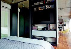 No quarto, a estante embutida exibe objetos e as bolas de futebol do morador. O projeto é do SuperLimão Studio